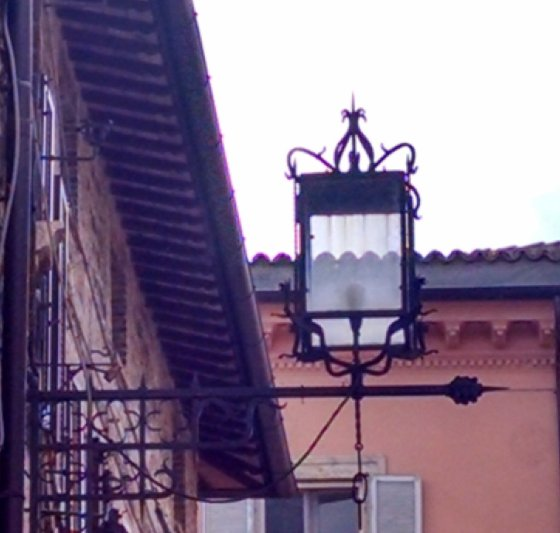 Streetlight posted on the side of a lamp in Assisi, Italy